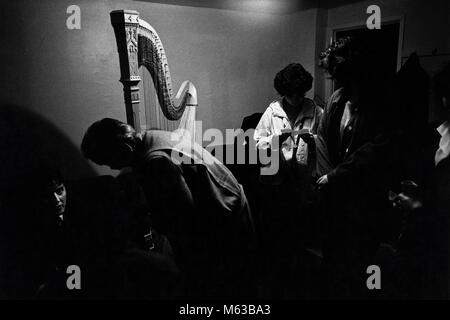 Back stage with harpist and concert harp at small eisteddfod in village hall Talsarnau Gwynedd Wales UK - Stock Image