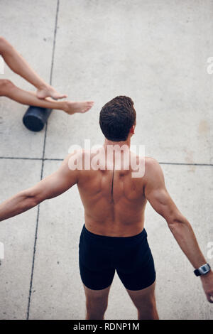 Athlete stretching at stadium - Stock Image
