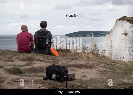 a man watching a hovering drone he is flying off the top of a cliff on the english coast. he's accompanied by another male sitting next to him - Stock Image