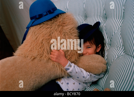 7 year old girl in hat hugging toy lion in hat - Stock Image