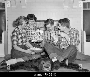 1950s GROUP TEENS POPPING POPCORN SMILE LAUGHING JOKING AROUND BEAR SKIN RUG FIREPLACE WEARING PLAID SHIRTS JEANS - j3343 LAN001 HARS TEAMWORK RUG PLEASED JOY LIFESTYLE CELEBRATION FEMALES HEALTHINESS HOME LIFE COPY SPACE FRIENDSHIP HALF-LENGTH PERSONS CLOTH MALES TEENAGE GIRL TEENAGE BOY PLAID DENIM SKIN POPCORN B&W HAPPINESS SHIRTS SMILES JOYFUL POPPING STYLISH TEENAGED BOBBY SOX BLUE JEANS JOKING JUVENILES TOGETHERNESS WIRE BASKET BLACK AND WHITE CAUCASIAN ETHNICITY OLD FASHIONED - Stock Image