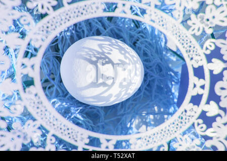 Easter. A lovely Easter card with an openwork oval frame through which beautiful shadows fall on a white egg. Blue background, top view. - Stock Image