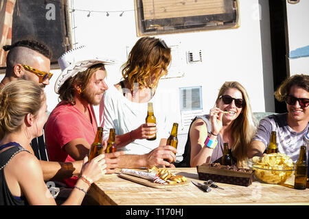Young caucasian people have fun all together drinking beers and eating food  sitting on a wooden table in rural concept lifestyle with old caravan in  - Stock Image
