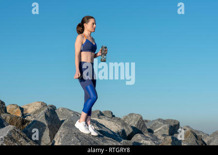 woman standing on rocks holding a glass sports water bottle - Stock Image