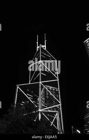 Bank of China Tower (Hong Kong) at night with illumiations with lit reflection of adjacent office building - Stock Image