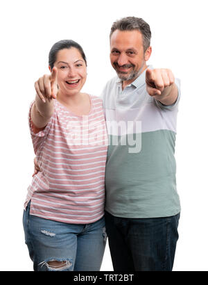 Friendly man and woman pointing at camera with index fingers as look concept isolated on white background - Stock Image