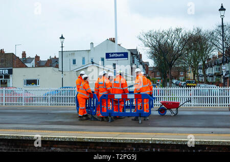 A gang of Railway Maintenance workers in orange overalls discussing a job on the Platform at Saltburn North Yorkshire - Stock Image