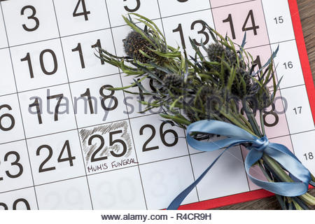 Mum's Funeral written on a calendar page and a posy of thistles - Stock Image