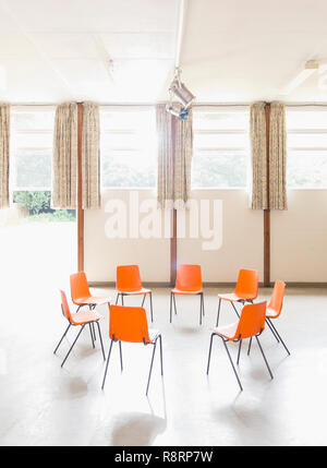 Orange chairs arranged in circle in community center - Stock Image