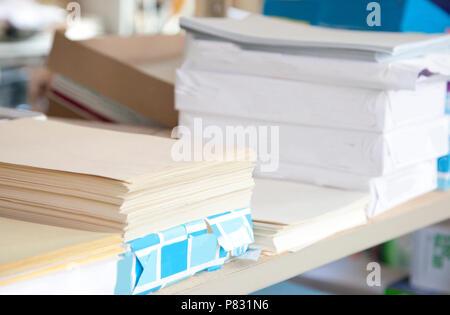 Office supplies stacked with reams of cream colored paper - Stock Image