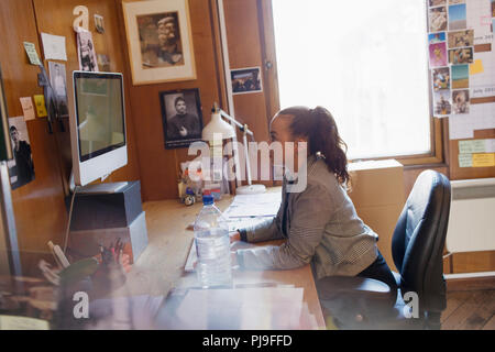 Creative businesswoman working at computer in office - Stock Image