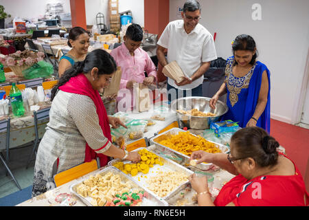 In the basement of the Dayaram Mandir in Queens, NYC, a man, boy and women prepare sweets to be given out after a Sunday morning Hindu prayer service. - Stock Image