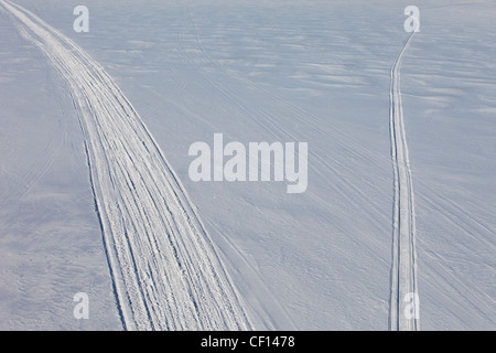 Snowmobile trails departing  to different directions - Stock Image