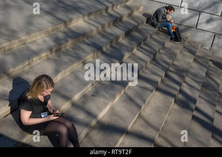 Two people sit and use their mobile phones on the steps beneath the Fourth Plinth in Trafalgar Square, on 26th February, in London, England. - Stock Image