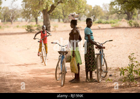 Samba village, Yako Province, Burkina Faso; schoolgirls on their way home from school wait in the shade for a friend. - Stock Image