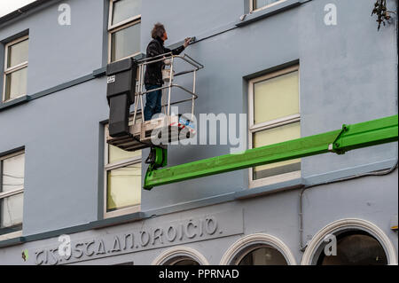 Painter and Decorator on an elevated platform painting a building in Bantry, West Cork, Ireland. - Stock Image