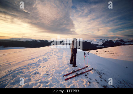 Skier looking at view while standing on Carpathian mountain - Stock Image