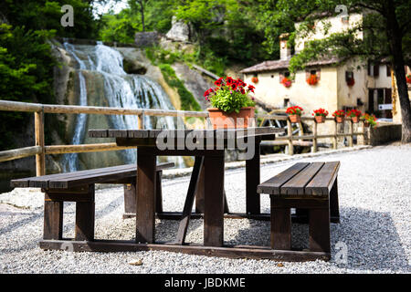 Bench with waterfall and a cottage with water mill in the background - Stock Image