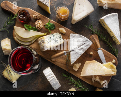 Cheese platter with different cheeses, fruits, nuts and wine on stone background. Top view. Tasty cheese starter. - Stock Image
