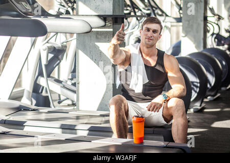 Portrait of satisfied athlete handsome masculine man sitting during treadmill exercise in gym, tired sportsman drinking water in sports hall. indoor, - Stock Image