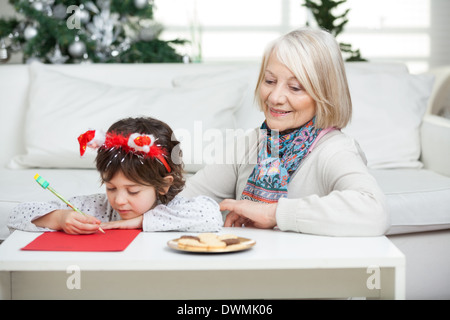 Grandmother Looking At Boy Writing Letter To Santa Claus - Stock Image