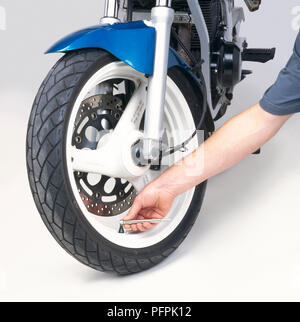 Checking the tyre pressure using a pressure gauge. - Stock Image