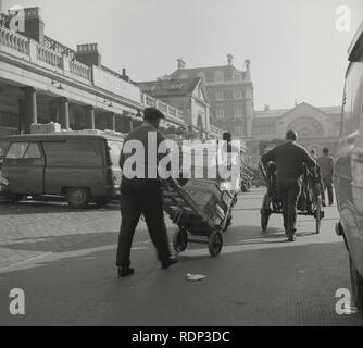 1950s, historical, early morning sunlight  as traders using wheel barrows move their produce at Covent Garden fruit and vegetable market, London, England, UK - Stock Image