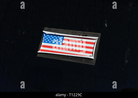 Stars and stripe sticker with curled up edges on a tinted car window - Stock Image