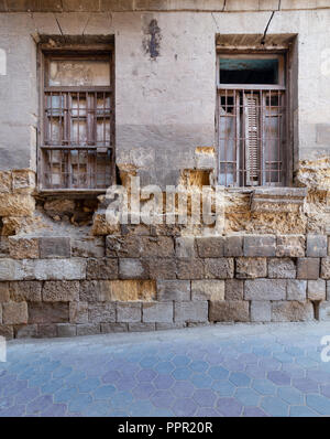 Two adjacent broken windows and grunge stone bricks wall in abandoned Darb El Labana district, Cairo, Egypt - Stock Image