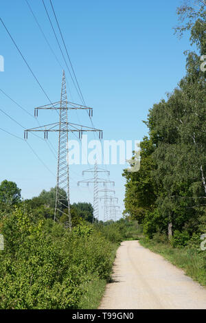 overhead high-voltage power line alongside footpath trough german countryside - Stock Image