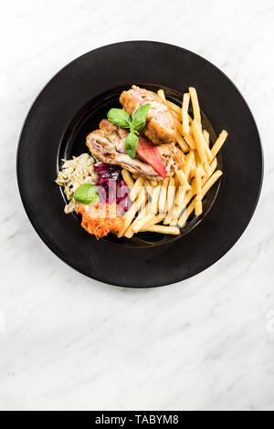 Chicken wraps with fries and salad, restaurant serving portion. - Stock Image