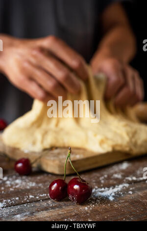 closeup of a young caucasian man kneading a piece of dough to prepare a coca de cireres, a cherry sweet flat cake typical of Catalonia, Spain, on a wo - Stock Image