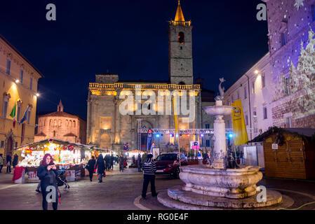 Ascoli Piceno, Italy - December 2018: People walking at night in winter in Piazza Arringo, a city square in Ascoli Piceno, Marche, Italy. - Stock Image