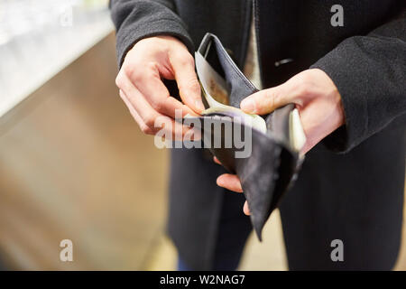 Man with wallet paying with cash in restaurant or retail - Stock Image