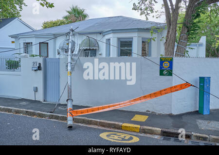 Fallen pole and wires unto a fence wall and house on street corner in southern suburbs of Cape Town, South Africa, January 25, 2019 - Stock Image