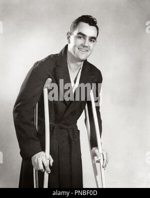 1940s SMILING MAN LOOKING AT CAMERA WEARING ROBE WALKING ON CRUTCHES - a3948 HAR001 HARS INSPIRATION UNITED STATES OF AMERICA MALES AILMENT CONFIDENCE B&W EYE CONTACT WOUND SUFFERING CHEERFUL RECOVERY SMILES WOUNDED RECOVERING POOR HEALTH AILING MID-ADULT MID-ADULT MAN BLACK AND WHITE CAUCASIAN ETHNICITY HAR001 OLD FASHIONED POST WAR - Stock Image