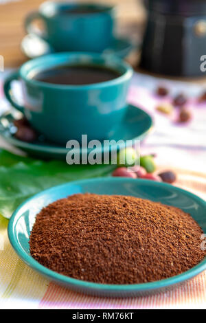 Fresh ground arabica coffee and cup with black coffee served outside with raw green, mature red and roasted coffee beans, decorated with green leaves  - Stock Image