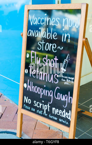 Forster, NSW, Australia-April 20, 2019: Flu shots vaccines advertisement board in front of farmacy in the city of Forster, a coastal town in the Great - Stock Image