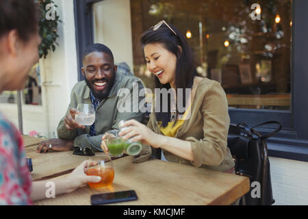 Smiling young friends drinking juice at sidewalk cafe - Stock Image