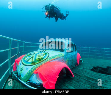 Female diver swimming over a VW Beetle attached to a submerged ship wreck - Stock Image