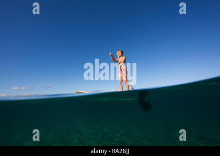 Split level view of a woman stand up paddling at Palauea, Maui, Hawaii. - Stock Image