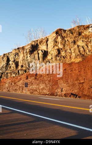 Road cut along highway 61 in northern Minnesota showing a basaltic lava flow on top of an underlying sedimentary - Stock Image
