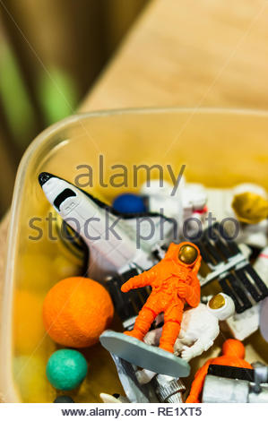 Poznan, Poland - December 9, 2018: Mix of space theme toys in a plastic box in soft focus. - Stock Image