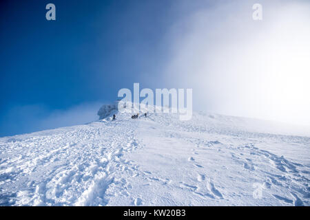 Stunning winter snow capped Penyfan in the Brecon Beacons, South Wales UK with walkers following the path to the - Stock Image
