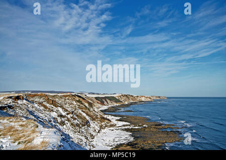Jackson's Bay, part of North Yorkshire's coastline north of Scarborough, in winter under a covering of snow. - Stock Image