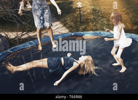 Happy family jumping on trampoline - Stock Image