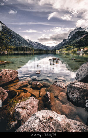 Amazing morning scenery on Hintersee Lake with alpine peaks reflected on the water during spring time - Stock Image