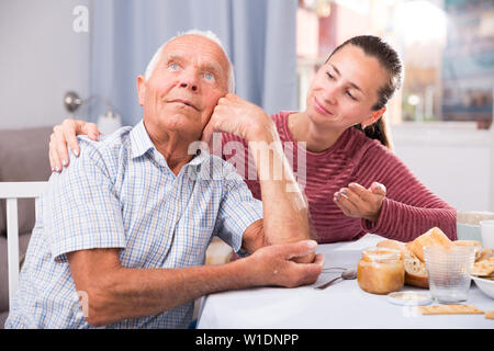 Portrait upset mature man sitting after conflict, daughter tries reconcile - Stock Image