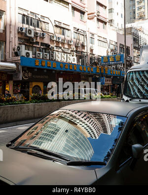 buildings reflected n a car window in Hong Kong - Stock Image