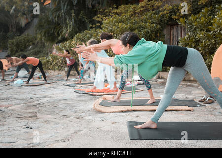 Yoga group - multiple people exercising outdoors. - Stock Image